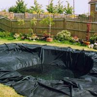 Pose du liner au fond du trou de bassin